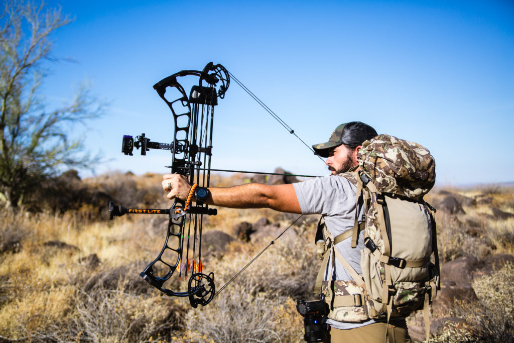 A bowhunter practicing long range bow shooting at the archery range.