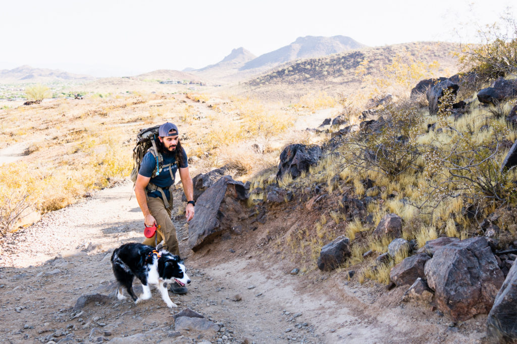Josh from Dialed in Hunter hiking a trail with a weighted pack and his dog