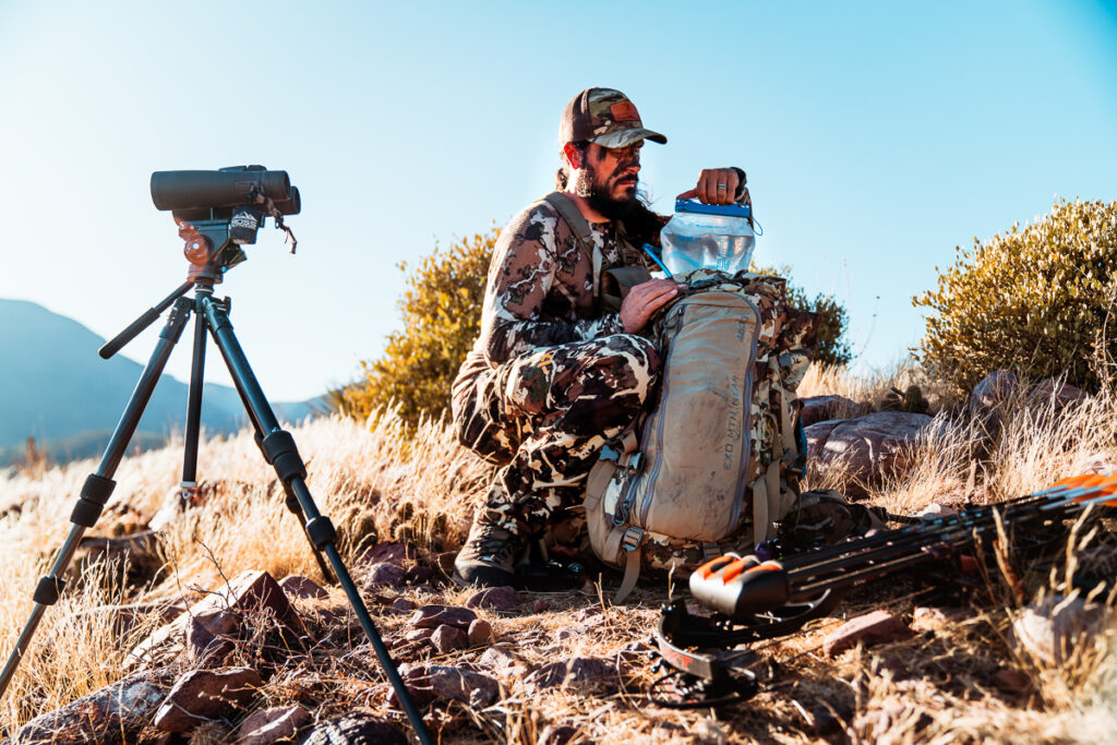 Josh Kirchner from Dialed in Hunter checking his water supply in his backpack on a spot and stalk archery hunt in the desert
