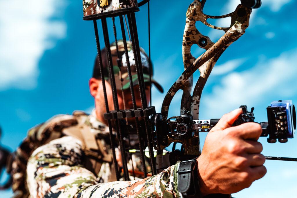 Archery hunter adjusting a black gold pro sight
