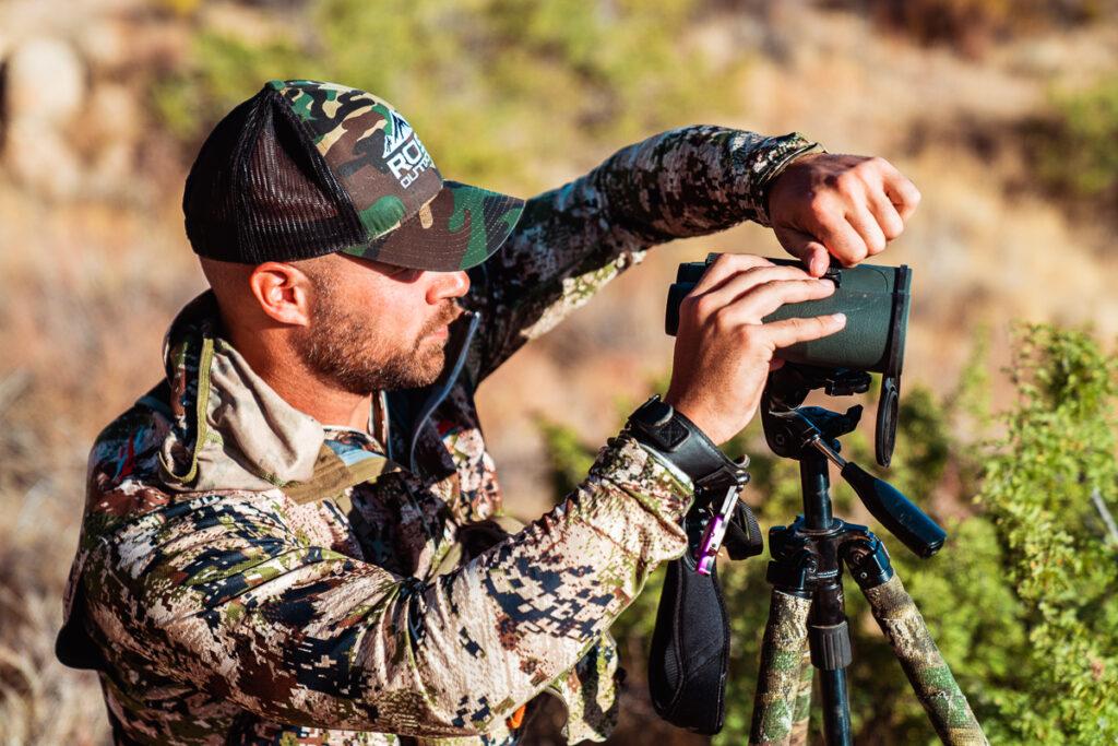 Hunter mounting his binoculars on a tripod head and tripod