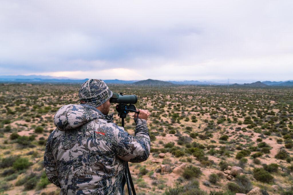 Hunter glassing the desert flats of Arizona from a tripod