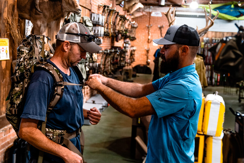 A customer at Ross Outdoors getting properly fitted for a hunting backpack